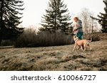 Stock photo young woman doing sports with her dog in summer park 610066727