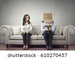 Small photo of Shy man sitting next to a woman with his head covered by a cardboard box