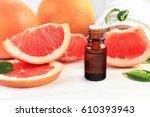 Small photo of Grapefruit fragrance oil in apothecary dark glass dropper bottle of liquid cosmetic product, fresh pink citrus fruit pulp in pieces. Sweet natural aromatherapy spa and health care