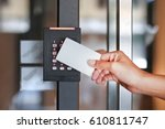 Small photo of Door access control - young woman holding a key card to lock and unlock door.