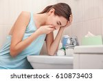 Small photo of Young vomiting woman near sink in bathroom