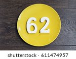 Small photo of The number sixty-two on the yellow plate and brown background.