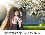 Small photo of Young girl blowing nose and sneezing in tissue in front of blooming fruit tree. Seasonal allergens affecting people