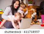 mom works at a laptop with... | Shutterstock . vector #611718557
