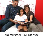 Family reclining in bed reading book together - stock photo