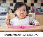 asian baby girl eating...   Shutterstock . vector #611861897