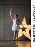 Small photo of Beautiful slim ballerina in white costume performing in studio with alight star