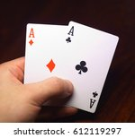 Small photo of human hand holding two aces on black wood table