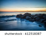 waves and a jetty at sunset in... | Shutterstock . vector #612518387