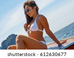 young woman in a bikini sits on ... | Shutterstock . vector #612630677