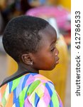 Small photo of KOUTAMMAKOU, TOGO - JAN 13, 2017: Unidentified Togolese little girl in colored shirt stands in the village. Togo children suffer of poverty due to the bad economy.