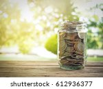 alarm clock and bottle of coins | Shutterstock . vector #612936377