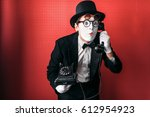 Small photo of Mime theater actor performing with old telephone