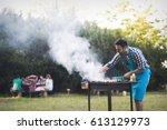 handsome man preparing barbecue ... | Shutterstock . vector #613129973