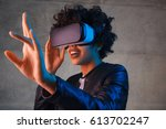 Stock photo amazed young woman touching the air during the vr experience horizontal studio shot 613702247