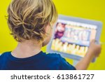 boy playing with digital tablet.... | Shutterstock . vector #613861727
