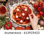 cooking pizza. hands adding... | Shutterstock . vector #613925423