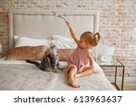 Stock photo little cute girl playing with kitten on sofa at home lifestyle child photo 613963637