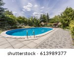 oval swimming pool in a garden... | Shutterstock . vector #613989377