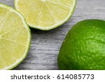 slices of lime in a wooden... | Shutterstock . vector #614085773