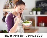 young woman eating fresh salad... | Shutterstock . vector #614426123