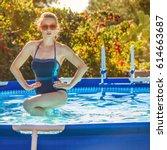 Small photo of Fun weekend alfresco. active woman in blue beachwear in the swimming pool doing aquafitness