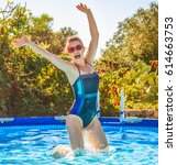 Small photo of Fun weekend alfresco. happy active woman in blue swimwear in the swimming pool jumping