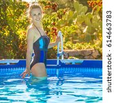 Small photo of Fun weekend alfresco. Portrait of smiling active woman in blue swimsuit standing in the swimming pool