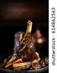 Small photo of Roasted lamb shank with root vegetables of parsnip, carrots and shallots. Selective focus with generous accommodation for copy space.