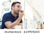 handsome young man eating a... | Shutterstock . vector #614905643
