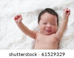 Happy newborn baby with arms up in the air. - stock photo