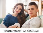 young couple on sofa looking at ... | Shutterstock . vector #615353063