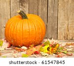 A Pumpkin And Autumn Leaves On...
