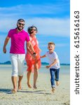 Small photo of Family of three running and jumping along the tropical beach, laughing and enjoying time all together