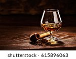 glass of cognac and pipe with... | Shutterstock . vector #615896063