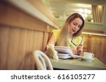 a girl in a coffee house is... | Shutterstock . vector #616105277