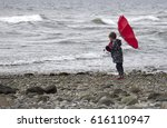 Small photo of small male child at the beach holding his red umbrella against the wind.