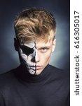 Small photo of Half face half skull man portrait in a dark