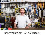 Small photo of portrait of young cheerful american man at the cash desk working in tool-ware shop
