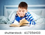 boy lying in bed with a book....   Shutterstock . vector #617356433