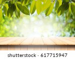 wood table with green leaves... | Shutterstock . vector #617715947