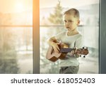young boy play on guitar at... | Shutterstock . vector #618052403