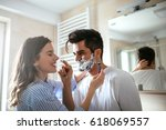 a handsome young man shaving in ... | Shutterstock . vector #618069557