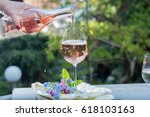 Stock photo waiter pouring a glass of cold rose wine outdoor terrace sunny day green garden background 618103163