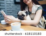 Stock photo adorable pug dog sitting in his owner s lap in cafe bar selective focus on dog 618110183