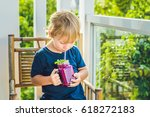 the boy holds smoothies from a...   Shutterstock . vector #618272183