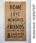 Small photo of Home is where love resides memories are created friends are always welcome and laughter never end-quote on brown wooden background.Many word on wood texture with white brick wall in coffee shop