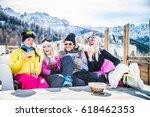 Small photo of Group of friends talking and having fun in a outdoor restaurant on winter holidays