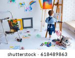 Small photo of Cute, serious and focused, white three years old boy in blue shirt and jeans apron drawing on canvas standing on the easel. Concept of early childhood education, talent, happy family or parenting
