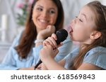 mom and daughter sing  | Shutterstock . vector #618569843